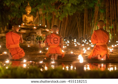 Asalha Puja Day ,Monks light candles and pray to buddha statue in Phan tao temple , Chiang mai ,Thailand.
