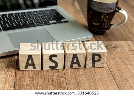 ASAP written on a wooden cube in front of a laptop - stock photo