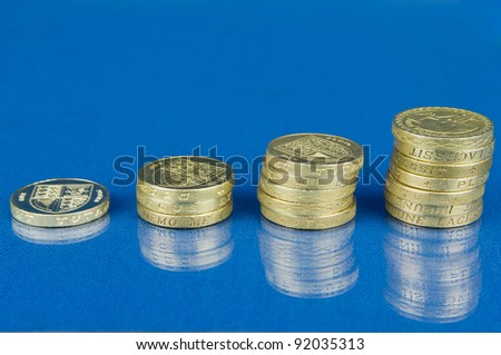Ascending stacks of coins isolated on blue background with reflection / Rising stack of pound coins - stock photo