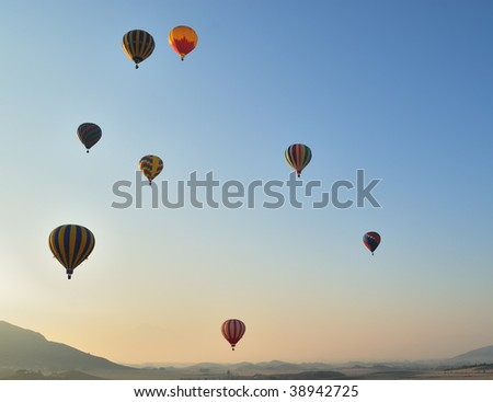 Ascension of hot air balloons at sunrise - stock photo