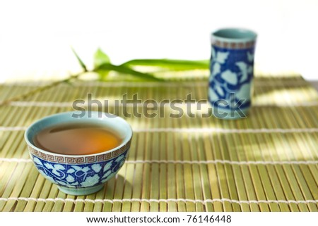 asean cup of tea and bamboo leaf  on the bamboo mat - stock photo