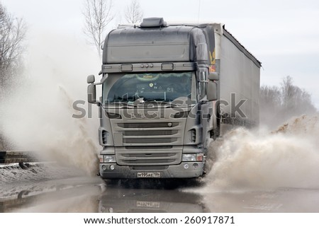 ASHA, RUSSIA - MARCH 15, 2015: Black semi-trailer truck Scania R420 at the city street during a strong flood. - stock photo