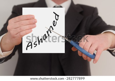 Ashamed, man in suit cutting text on paper with scissors