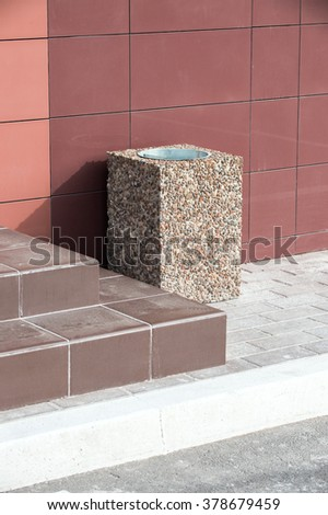 ashcan decorated with natural stone stands near the house been charged granite - stock photo