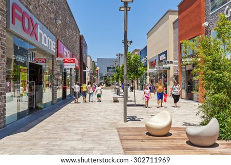 ASHDOD, ISRAEL - JULY 22, 2015: People among shops and boutiques in opened mall - owned by BIG Shopping Centers Ltd., founded in 1994 and operates in four countries - Israel, USA, India and Serbia. - stock photo