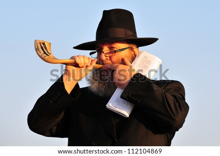 ASHDOD - SEPTEMBER 09: Jewish orthodox man blows the shofar during the Jewish ceremony of Tashlich to begin the Jewish new year on September 9 2010 in Ashdod, Israel. - stock photo