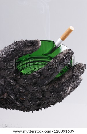 Ashed hand holding green ashtray with a fired cigarette which shows that smoking is harmful/Let's smoke!