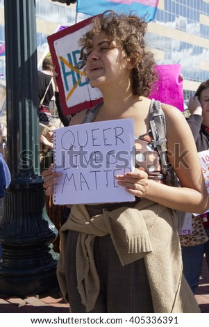 "Asheville, North Carolina, USA - April 2, 2016:  A woman holds up a sign saying ""Queer Lives Matter"" at a HB2 legislation protest rally"