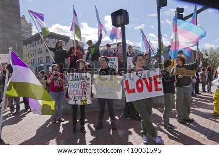 Asheville, North Carolina, USA - April 2, 2016: LGBT protest rally against the HB2 Law in North Carolina with symbolic flags, transgender symbols and signs about bathroom restrictions, pride, and love - stock photo
