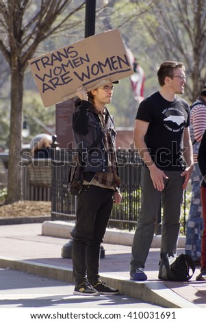 "Asheville, North Carolina, USA - April 2, 2016: Sign at a LGBT protest rally against the HB2 Law in North Carolina say ""Trans women are women"" on April 2, 2016 in downtown Ashevile, NC"
