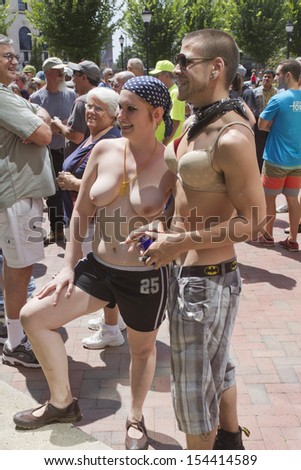 ASHEVILLE, NORTH CAROLINA, USA - AUGUST 25, 2013: A crowd gathers near a topless young woman accompanied by a young man wearing a bra at the Go Topless Rally in downtown Asheville    - stock photo