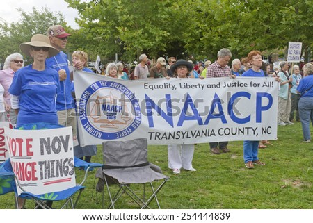 Asheville, North Carolina, USA - August 4, 2014: Crowd of mostly older caucasian people hold signs promoting the NAACP and voting at a Moral Monday rally in on August 4, 2014 in downtown Asheville - stock photo