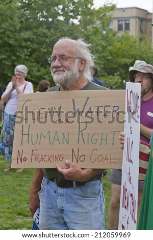 Asheville, North Carolina, USA - August 4, 2014:  Older man holds a sign saying that clean water is a human right, no fracking, no coal on August 4, 2014 at a Moral Monday rally in Asheville, NC - stock photo