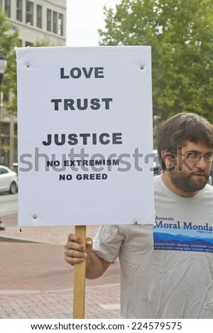 Asheville, North Carolina, USA - August 4, 2014: Young man at a Moral Monday rally holds up a sign calling for love, trust, justice and no extremism or greed on August 4, 2014 in downtown Asheville - stock photo