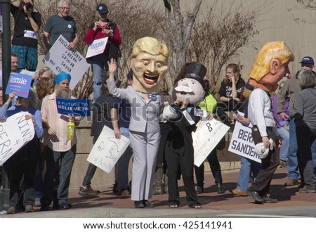 Asheville, North Carolina, USA - February 28, 2016:  Effigies of Hillary Clinton with Mr. Monopoly and bags of money as Donald Trump is excluded and a crowd of Bernie Sanders supporters watch