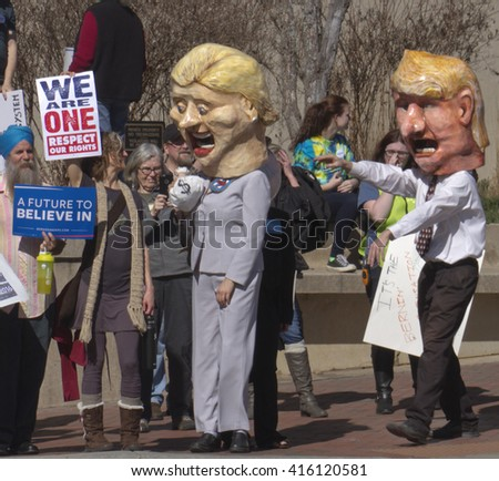Asheville, North Carolina, USA - February 28, 2016:  Humorous effigies of Hillary Clinton with a moneybag as Donald Trump reaches for her and Bernie Sanders supporters watch