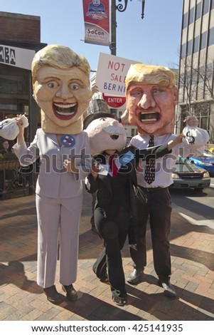 Asheville, North Carolina, USA - February 28, 2016:  Parody of Trump and Clinton holding bags of money as Mr. Monopoly peeks out from behind them in front of a sign saying Bernie is not for sale