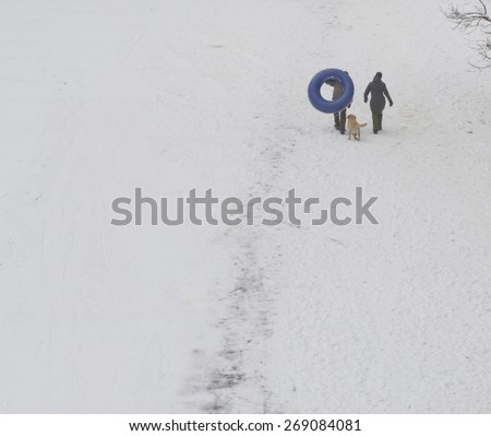 Asheville, North Carolina, USA - February 26, 2015: Two people with a dog following behind carry a large inner tube up a snowy winter hill prior to sledding down on it - stock photo