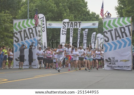 Asheville, North Carolina, USA - July 26, 2014: Color Run Runners wearing colorful t-shirts and headbands burst enthusiastically from the starting line as the race begins in downtown Asheville, NC   - stock photo