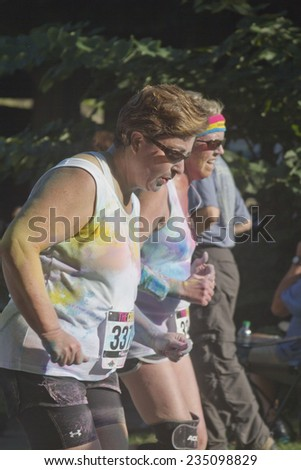Asheville, North Carolina, USA - July 26, 2014: People splattered with dye run neck and neck in the the happy Asheville 5K Color Run on July 26, 2014 in downtown Asheville, NC  - stock photo