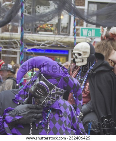 Asheville, North Carolina, USA - March 2, 2014: Man in a colorful Mardi Gras Fool costume laughs as death lurks in the background in the annual Mardi Gras Parade on March 2, 2014 in Asheville, NC  - stock photo