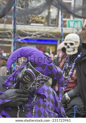 Asheville, North Carolina, USA - March 2, 2014: Man in a Mardi Gras Fool costume laughs as death lurks behind in the annual Mardi Gras Parade on March 2, 2014 on Wall Street in downtown Asheville, NC - stock photo