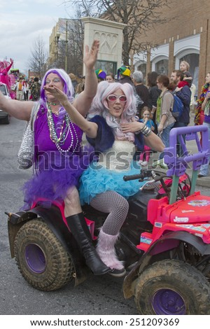 Asheville, North Carolina, USA - March 2, 2014:  People colorful costumes give pageant style waves and fashionably ham it up in the Mardi Gras parade on March 2, 2014 in downtown Ashevile, NC  - stock photo