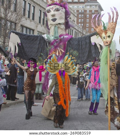 Asheville, North Carolina, USA - March 2, 2014: People wearing colorful and creative costumes march next to a large puppet and entertain spectators in the annual Mardi Gras parade - stock photo