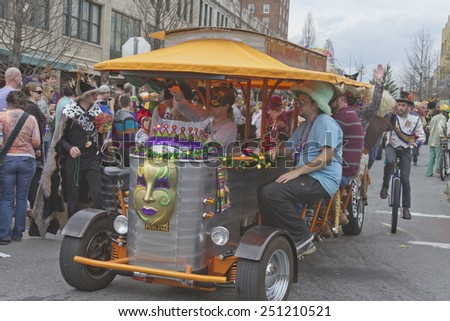 Asheville, North Carolina, USA - March 2, 2014:  The Asheville PubCycle, a combination bar and street vehicle pedaled along by its patrons, rolls along next to a unicyclist in the Mardi Gras parade  - stock photo