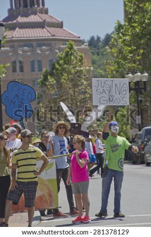 Asheville, North Carolina, USA - May 23, 2015: American activists hold signs and protest Monsanto and Genetically modified foods in a nationwide event on on May 23, 2015 in downtown Asheville, NC   - stock photo