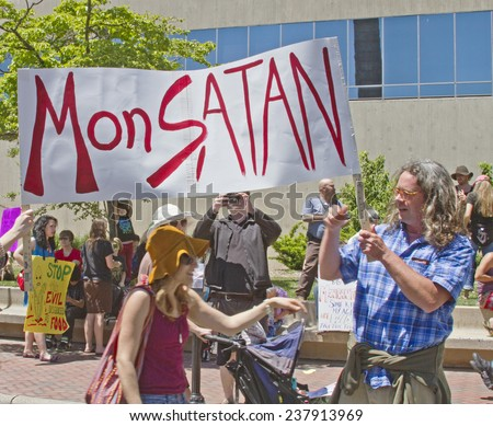 "Asheville, North Carolina, USA - May 25, 2013: Genetically modified food protesters hold up a sign calling Monsanto ""MonSATAN""at a GMO protest rally on May 25, 2013 in downtown Asheville, NC - stock photo"