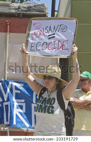 "Asheville, North Carolina, USA - May 24, 2014:  Young woman holds up a sign saying ""MONSANTO = ECOCIDE"" at a GMO foods protest rally on May 24, 2014 in downtown Asheville, NC"