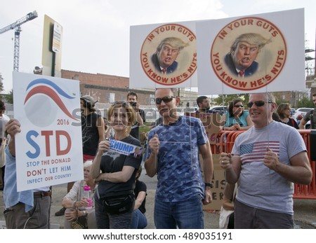 Asheville, North Carolina, USA: September 12, 2016: Protesters hold signs at a Donald Trump Rally saying not to let him infect our country and in your guts you know he's nuts, in Asheville, NC