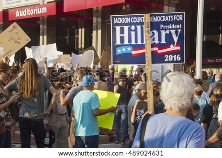 Asheville, North Carolina, USA: September 12, 2016: Senior Woman holds a Hillary Clinton sign among a crowd of protesters at a Donald Trump campaign rally on September 12, 2016 in Asheville, NC
