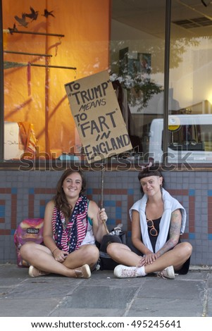 "Asheville, North Carolina, USA: September 12, 2016: Two young women hold a sign at a Donald Trump campaign rally saying  ""To Trump Means to Fart in England"" on September 12, 2016 in Asheville, NC"