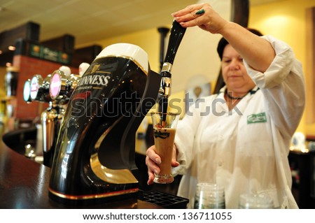 ASHKELON - JULY 27:Woman bartender pours a glass of beer on July 27 2009 in Ashkelon, Israel.Beer is the oldest alchoholic beverage and has been around since at least the ancient Sumerians of 2600 B.C - stock photo