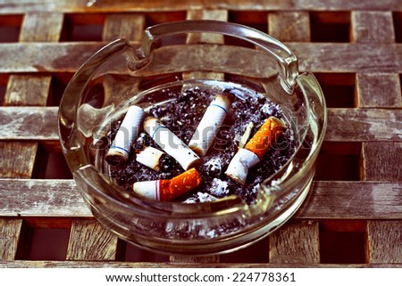 Ashtray and cigarettes butts close-up in retro filter effect - stock photo