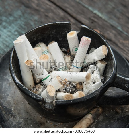 Ashtray and Cigarettes Close-up on Wooden Background - stock photo
