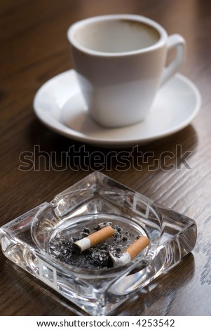 Ashtray and empty coffee cup on the cafe table. Shallow depth of field (focus on the cigarette butt). - stock photo