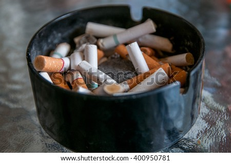 ashtray dingy light with many  cigarette stub. - stock photo