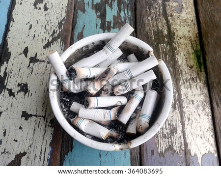 Ashtray full of butt cigarettes on wooden background. Smoking is the leading cause of cancer. - stock photo