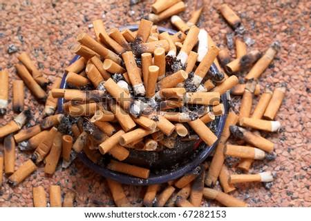 ashtray full of cigarettes close-up - stock photo