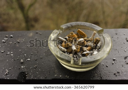 ashtray full of cigarettes stubs on a wooden texture - stock photo