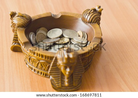 Ashtray in the form of sphinxes with a monetary trifle - stock photo