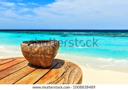 Ashtray made of coconut is on a beach table