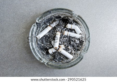 Ashtray with full of smoked cigarettes - stock photo