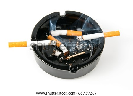 Ashtray with smoking cigarettes on it and butts inside - stock photo