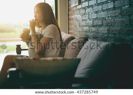 asia Attractive woman sitting on the couch at coffee shop - stock photo