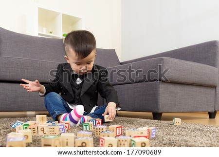 Asia baby boy play wooden toy block - stock photo