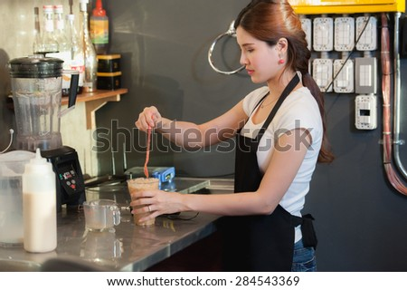 asia beautiful female bartender makes iced coffee on cafe - stock photo